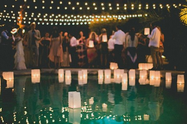 Floating lights in a pool or pond add a charming touch to any wedding
