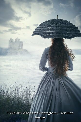 Trevillion Images - woman-standing-in-gray-dress-and-umbrella-looking