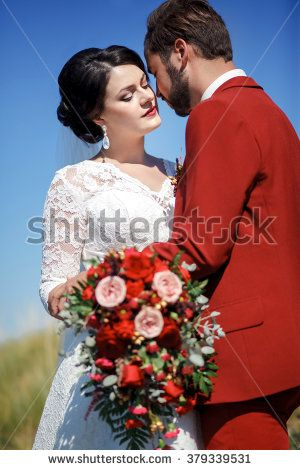 Bride and groom, lovely couple outdoor, great chic wedding bridal bouquet with red flowers. Blue sky and green grass.  Vertical beauty portrait of a couple. Stylish man with beard and mustache.
