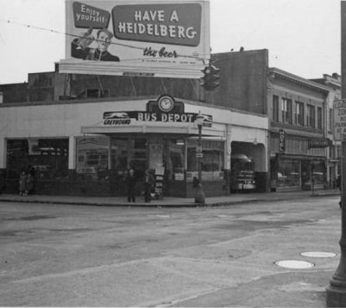 """Bus station at corner of 5th & Main, February 11, 1952. Heidelberg Beer billboard sign. Scenes of Vancouver before I-5. From the Munro-Watson Collection. Donated by Joan Munro Watson, daughter of Francis Tresyhair and Sarah """"Nancy"""" Annie Munro. F.T. Munro owned an automobile repair business (Munro & Bolma) and worked as a photographer on the side. Mr. Munro was also a member and president of the Vancouver Camera Club. The Munro family lived on and worked a 10 acre prune orchard and chicken…"""