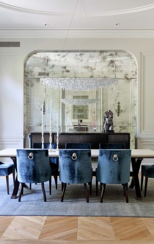 Antiqued mirror blue velvet dining chairs with hardware detail and herringbone flooring in a traditional dining room by studio william hefner