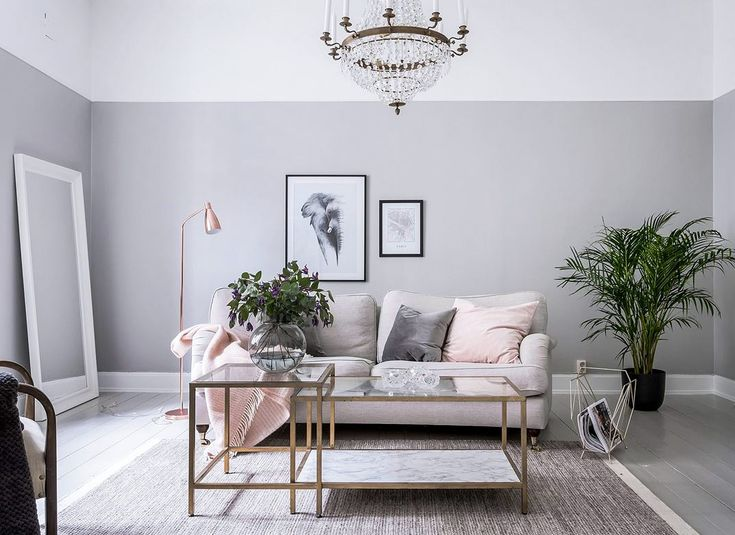 Grey painted wall in livingroom, green plants and pink cushions. Chrystal chandelier Ideas how to decorate with the biggest trends 2018.