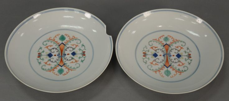 Pair of Chinese porcelain dishes with scrolling vines and designs in the center and back, having Tongzhi six character mark on bottom.