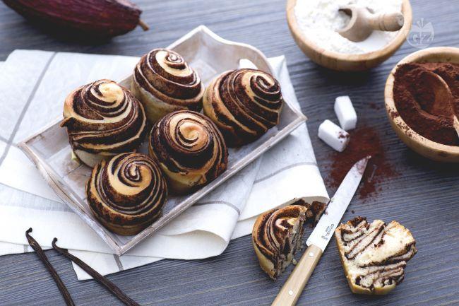le brioches variegate al cacao si presentano a forma di rosa grazie all'impasto alla vaniglia e al cacao sovrapposti e arrotolati su loro stessi