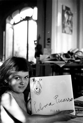 Picasso's daughter, Paloma, proudly holds up her latest drawing, July 13th, 1957 © David Douglas Duncan.