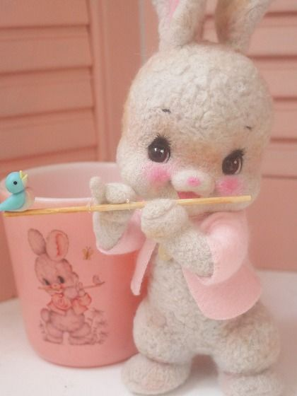 Vintage squeaky toy bunny and plastic bunny cup.