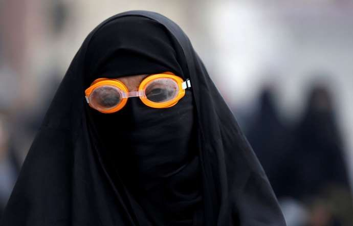 A female protester wears goggles to protect herself from tear gas - Hasan Jamali/AP