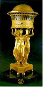 Sobremesa en bronce dorado. Sobre un pedestal triangular, las figuras de «Las tres Gracias» sostienen un cestillo con tapa que aloja la esfera de discos rotativos del reloj.