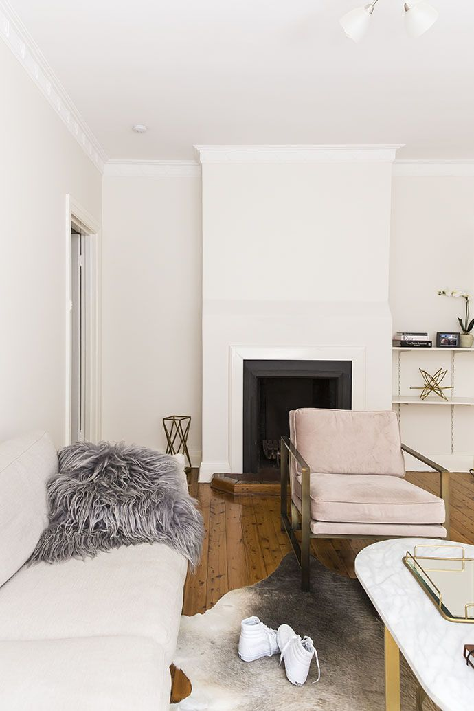Cozy living space with a fireplace, a daybed, and a blush armchair