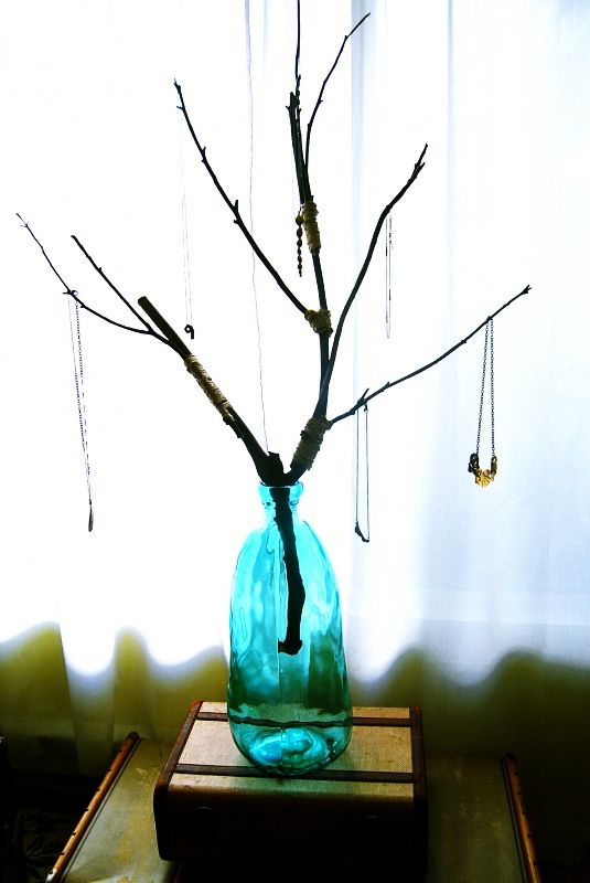 Think I'd like to try something like this DIY jewelry tree from Mr. Kate. It's a great starting point - maybe add small river rocks to the bottle and spray paint the twigs?