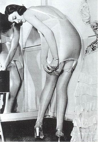 """In 1938 a woman reveals how she manages to look so sleek in a long, bias-cut dress. Her all-in-one stretch corselet was designed to hold in the hips and waist, and would have been made out of elasticised cotton-satin. Flesh-coloured silk stockings were fastened to suspenders, and corselets often had low backs that could work with evening styles."""