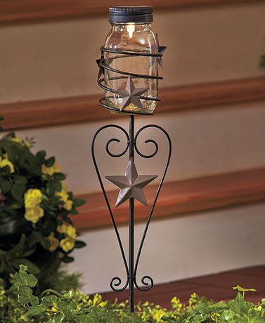 """The Country Mason Jar Solar Stake emits a warm glow at dusk, lighting up the pathway to your door. Charming rustic icons embellish the stand and spiral jar holder. On/off switch. 5-1/2""""W x 4-1/2""""D x 29""""H, including the 3"""" stake. Metal and glass."""