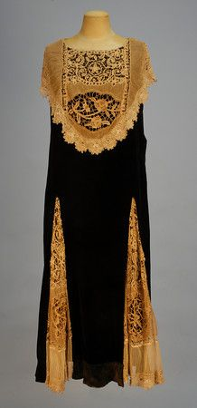 "SADIE NEMSER VELVET and LACE TEA GOWN, LATE 1920's. Sleeveless black velvet A-line having large bib front draping the shoulder and forming back collar, and two large front skirt gores pieced in various laces including Irish crochet, tape and needlepoint laces, side closure. Label ""Nemser Original Model"". Front"