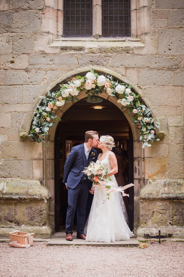 Beautiful soft peach wedding at Prestwold Hall. Floral design by Bloom Fleuriste, photography by Sarah Salotti. Church floral arch includes avalanche roses, white hydrangea, peach hypericum, sedum and eucalyptus.
