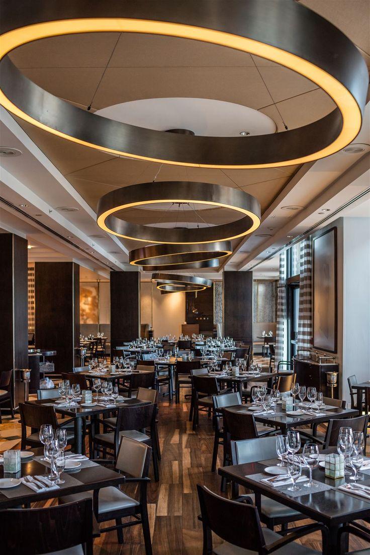 Large metal ring pendants in the Ocean Restaurant located at the Marriott Harbor Beach Resort & Spa in Fort Lauderdale spark up good appetite. #light #lighting #design #designlighting #interior #chandelier #hospitality #hotel #restaurant #restaurantinteriors #restaurantlightingideas