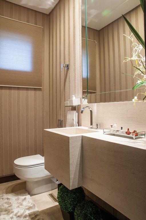 O lavabo recebeu bancada em limestone Mont Charmont, com cuba esculpida na pedra, espelho bisotado e papel de parede de seda com listras em veludo na cor nude.