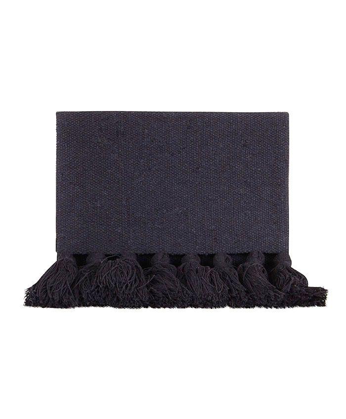 Clutch de tela en color negro. Solapa decorada con borlas de flecos. Cierre con dos botones de imán.