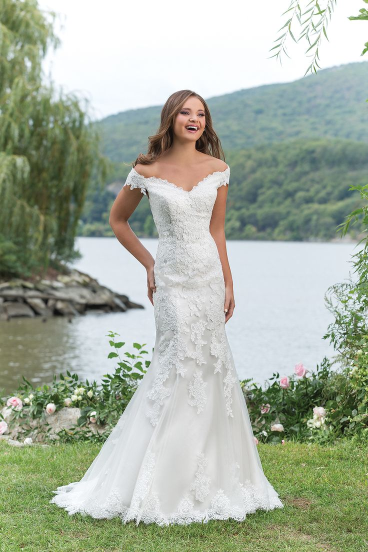 Sweetheart Gowns Style 6155: This flirty fit and flare wedding gown has an off the shoulder neckline highlighted with tulle and corded lace, tulle and satin covered buttons, and a sweep train.