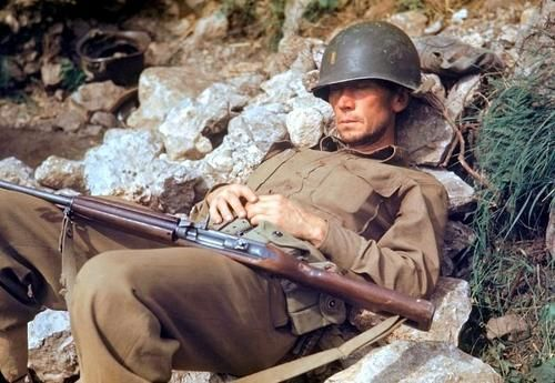 An American soldier (2nd lieutenant), armed with an M1 carbine, catches a little nap at a break in the advance, on a hillside in the outskirts of Rome, Italy.