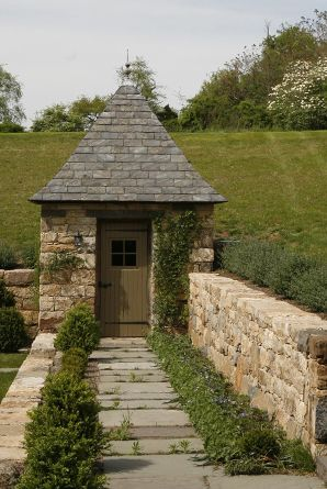charming little garden building integrated into this stone wall; love!