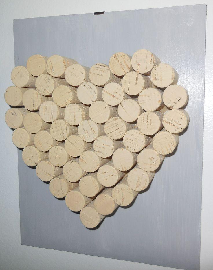 cuore fatto con tappi di sughero incollati sul un cartone pesante colorato di grigio chiaro.