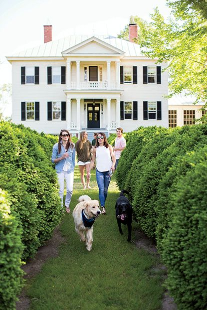 Bance family members strolling with their dogs in front of their Greek Revival plantation home in Virginia. Photo by Patricia Lyons. | Garden & Gun
