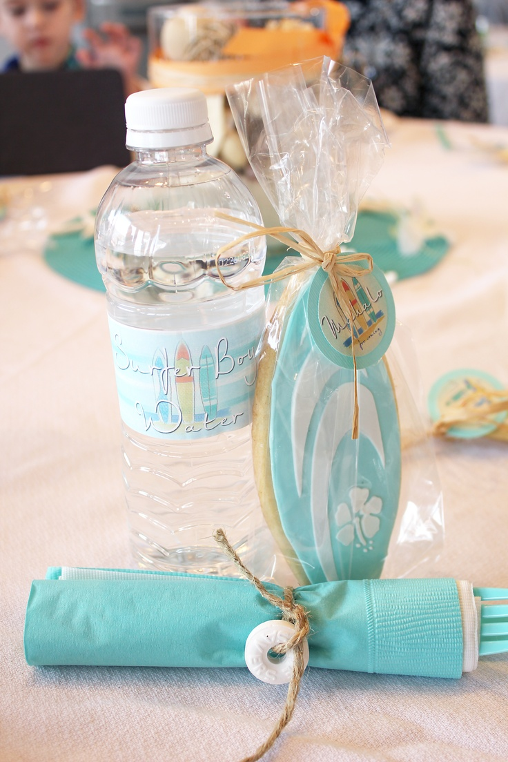 hawaiian themed baby shower details - surfer boy water bottles, life saver utensils and surf board cookies.