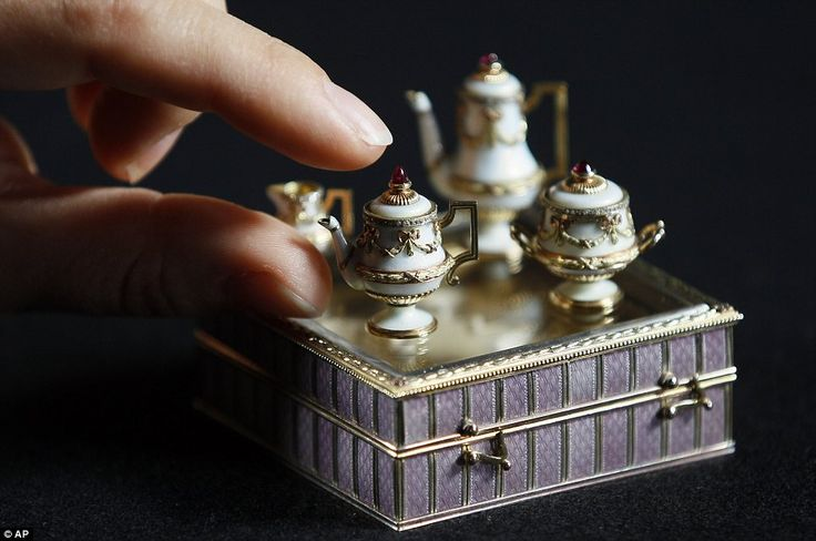 A miniature Fabergé tea set that is among more than 100 items collected by the Royals since the reign of Queen Victoria goes on display at Buckingham Palace