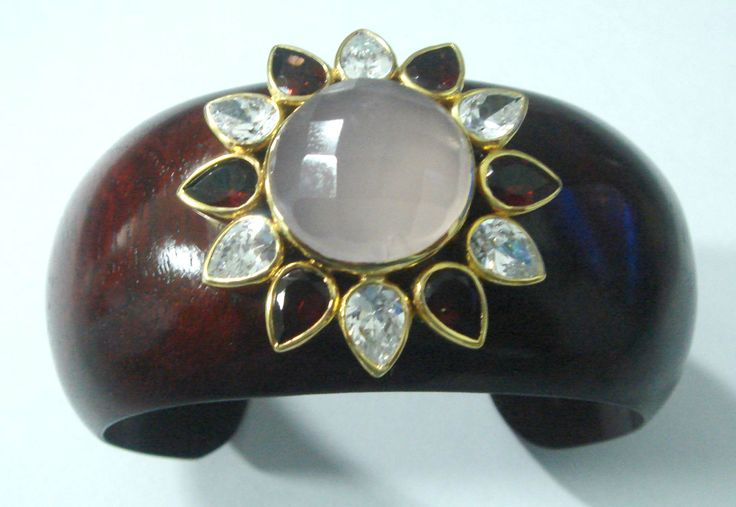 Artisan wood cuff with flower design. Gold plated silver flower studded with large faceted Sri Lankan moonstone center stone. The leaves are studded with alternating pear cut and faceted ruby red and clear high quality cubic zirconia.