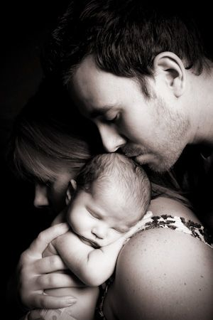 Daddy kissing baby's head over mom's shoulder