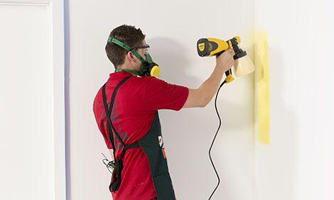 spraying a wall using a paint sprayer