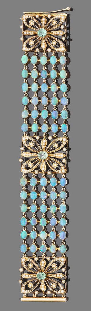 An opal, demantoid garnet and half pearl bracelet.  The bracelet designed as five rows of collet-set cabochon opals, between square openwork panels of floral design, each set throughout with half-pearls and a central oval-cut demantoid garnet