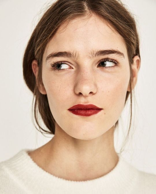 Matte but radiant skin, soft fluffy brows, minimal shadow, natural lashes, bold matte lip