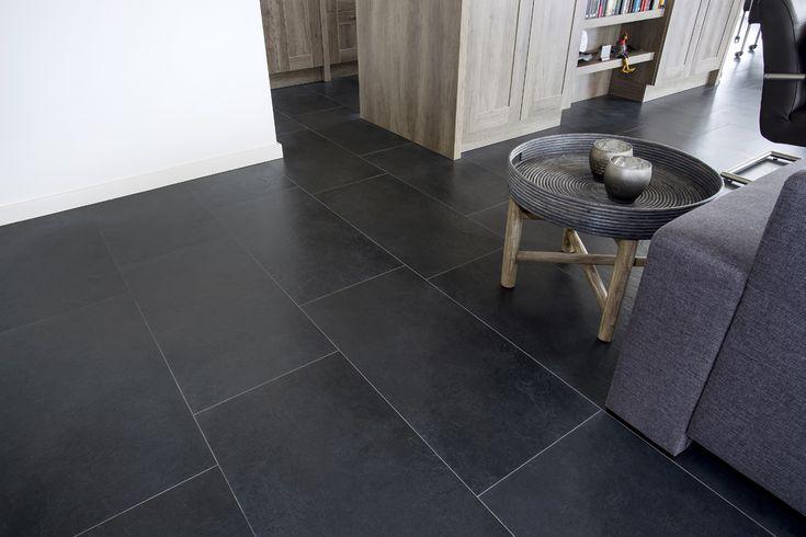 De donkere tegels geven de ruimtelijke woonkamer een hele chique uitstraling. Juist omdat de kamer zo groot is, kan er een donkere, natuurstenen vloer worden gebruikt.