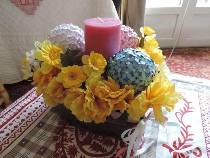 Composition de fleurs artificielles, boules de polystyrène piquées de fleurs en papier et bougie.