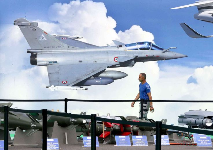 Le Salon du Bourget 2015. An employee walks past a poster on the Dassault Rafale pavilion.