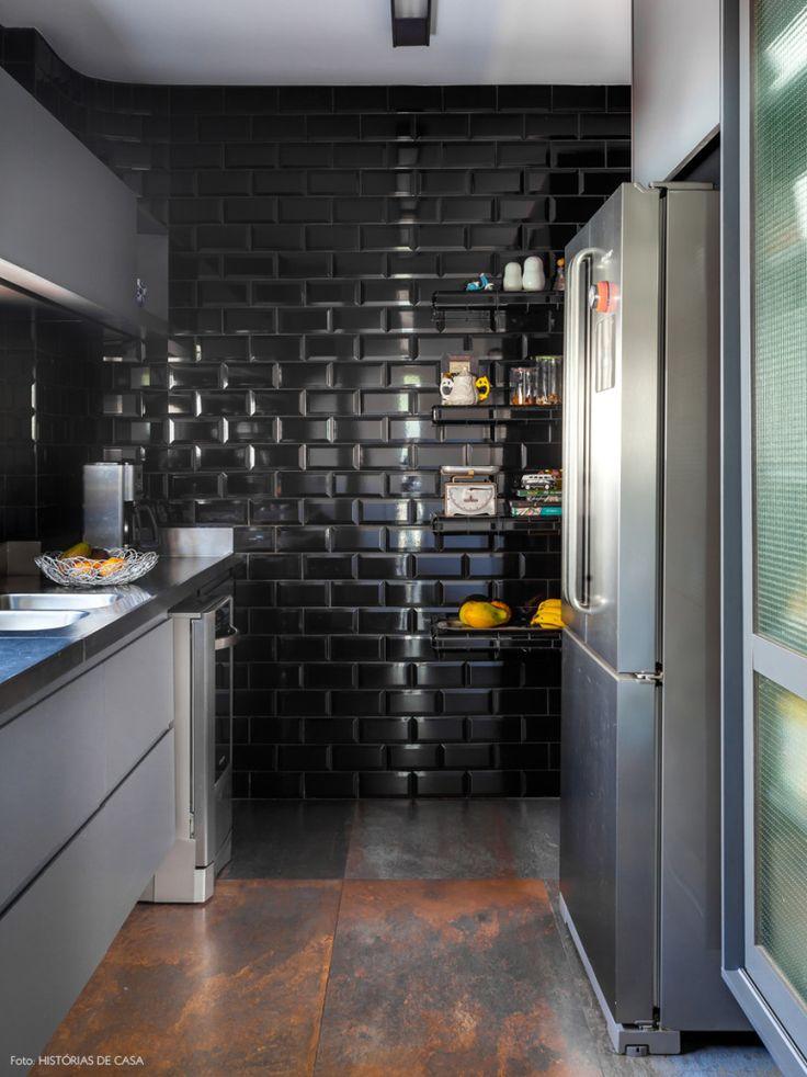 Cozinha de estilo industrial com subway tiles preto e armário com portas de vidro. Projeto: Estúdio Ka.