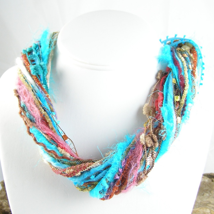 Fuzzy necklace made with yarn and torn fabric strips.