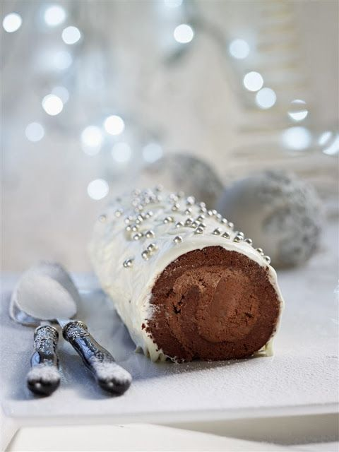 White Christmas chocolate log with chestnut filling, covered with white chocolate and cream cheese frosting
