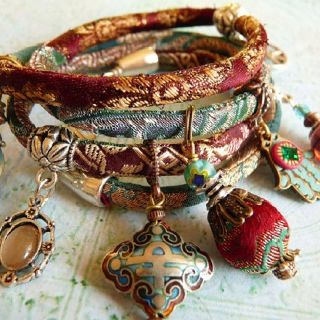 This is memory wire inside a thin sewn sleeve of fancy fabric. Add charms with large jump rings, and pretty end caps for the tips of the bracele...................