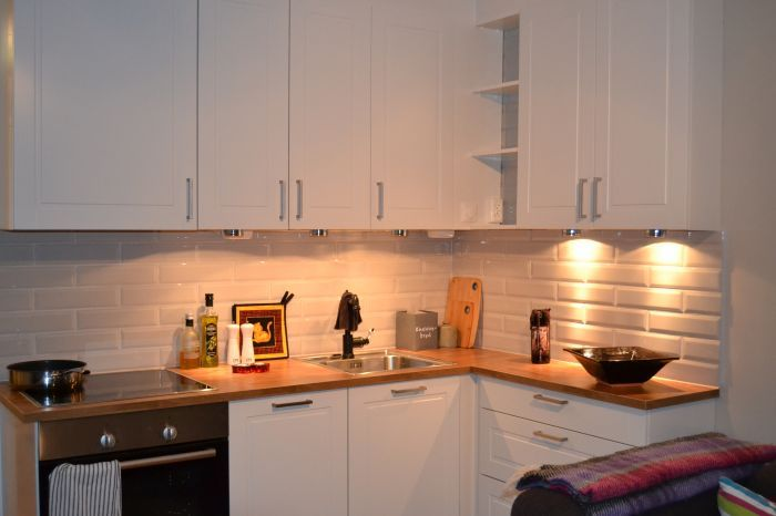 Montering av #kjøkken. Hvite skapfronter, heltre benkeplate og spottbelysning over benken.
