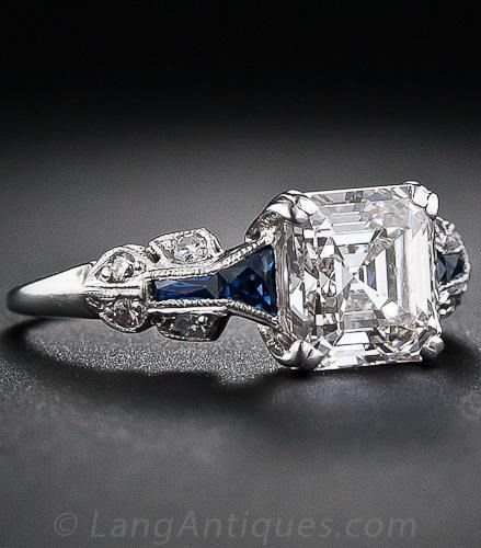 1.75 Carat Asscher-Cut Diamond Art Deco Ring.  A glorious and glistening classic square emerald-cut - aka Asscher-cut - diamond is the star attraction of this showstopping engagement ring, crafted in platinum and accented with calibre-cut faceted sapphires - circa 1930s. A ravishing, rare and original Art Deco engagement ring for a lucky lady of the same qualities.