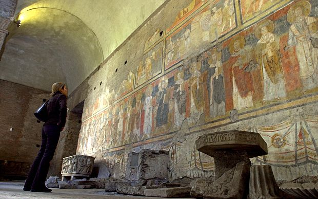 A visitor looks at a fresco, Christ on throne with Saints, believed to date back to 757 A.D., in Santa Maria Antiqua monument