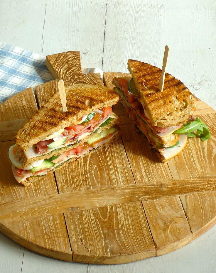 Club Sandwich met kipfile, bacon, tomaat, komkommer, ei , ui en sla en een dressing van pesto, joghurt en mayo