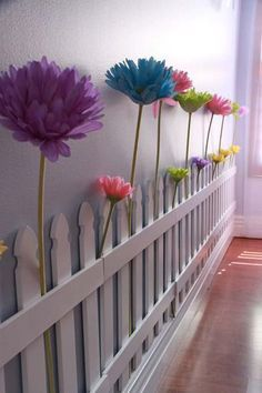 Bring white fence to indoor, and then decorate it with giant flowers | 26 Cute Ideas To Add Fun To a Child Room