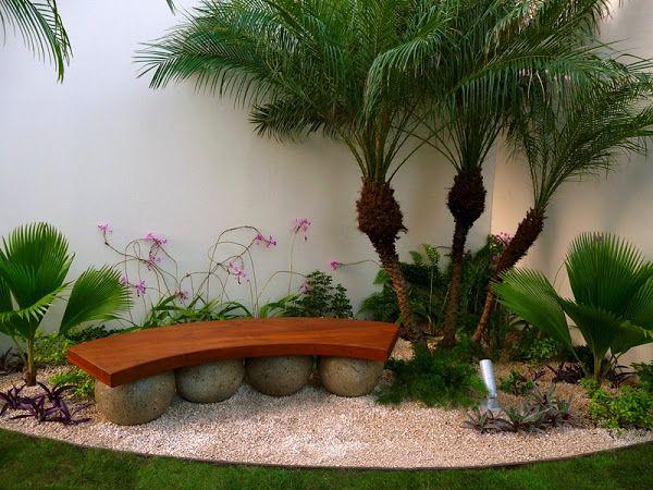 diseño de jardines de lujo - banca de madera tropical sobre esferas de piedra