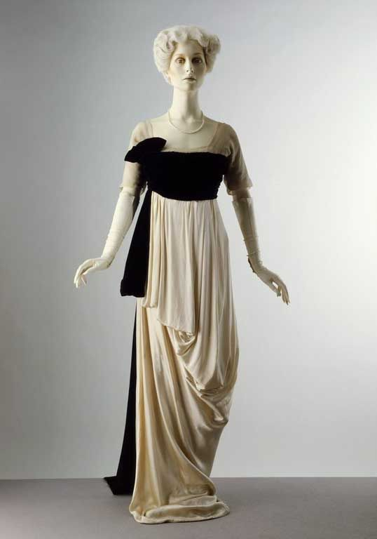 """1912 - evening dress. This dress has classical Greek (or is it """"Grecian"""") drapery and simplicity. I'm not sure if it could be worn to a formal occasion today, but the contrast and drapery are elegant. Her sash and over-bodice may have a train."""