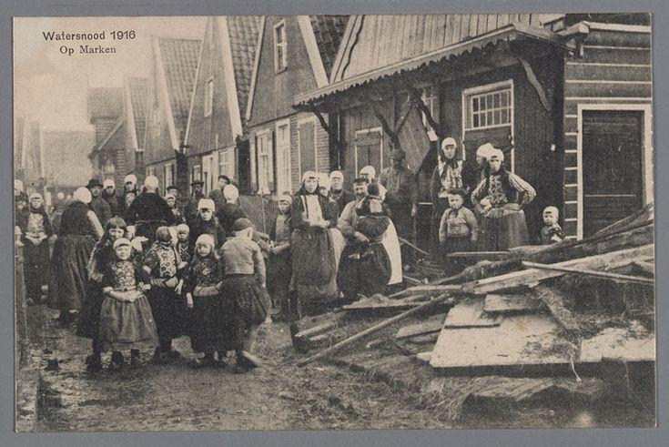 Grote groep dorpsbewoners in klederdracht na de watersnoodramp. Kerkbuurt, de kroeg, in 1925 gesloopt en herbouwd als winkel door C. Vlasbloem. Watersnood 1916 #NoordHolland #Marken