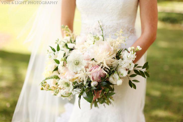 a springtime loose, organic bridal bouquet of light pink peony, peach stock, white stock, white scabiosa, white astilbe, snow on the mountain, light pink ranunculus, white majolik spray rose, fern, elm & jasmine vine.