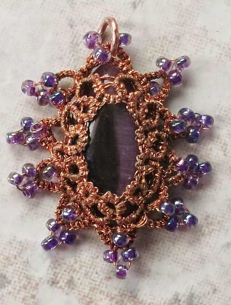 """Coppery      This pendent was tatted with two strands of copper sewing thread around a purple cats-eye.  The pendent measures 1"""" X 1.25""""."""